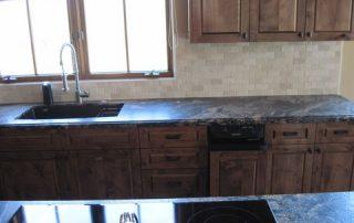 Dark Countertops with Dark Wood and Travertine tiles